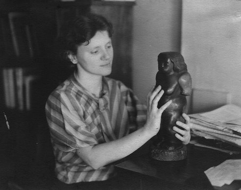 Black and white photo of a young woman in a striped shirt, reaching her arms out to touch a small statue to the right of her of a nude female figure. The young woman has a short haircut and smiles while looking down at the sculpture.