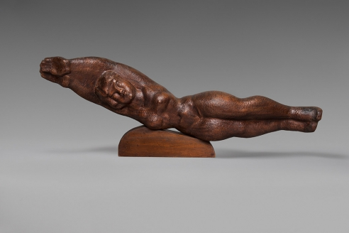 Medium dark wood sculpture of a female form lying on its side in a diving like position. The arms and legs are both conjoined together and her waist is raised slightly off of the small wood mount.