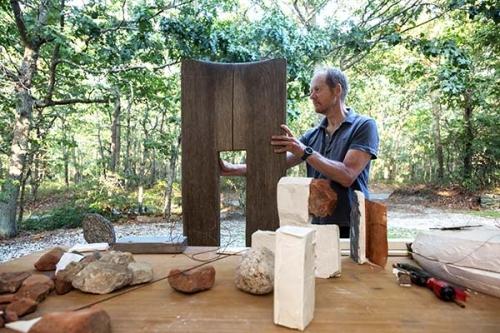 Mark Webber works on a wood sculpture outside his studio Credit: Francine Fleischer