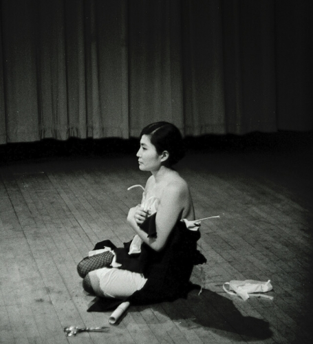 Yoko Ono performing Cut Piece (1964) at Carnegie Recital Hall, NYC. March 25, 1965. Photo by Minoru Niizuma ©Yoko Ono⁠