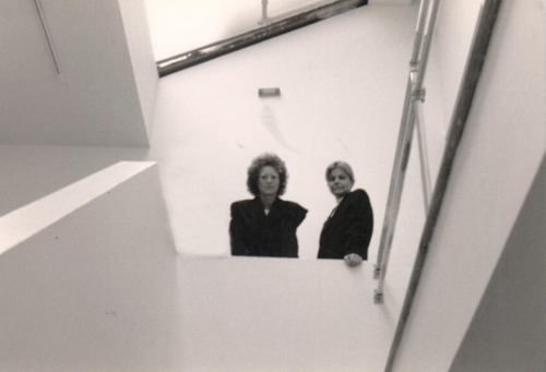Cofounders Helene Winer and Janelle Reiring gazing down from staircase