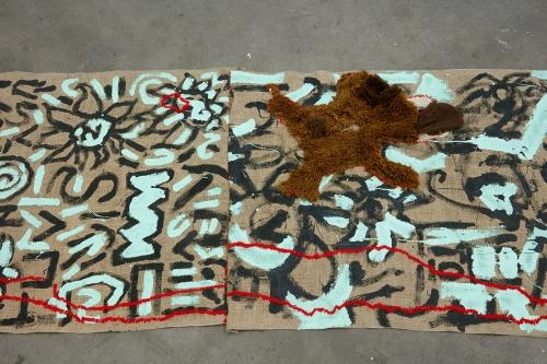 "Alex Chaves, ""Amerikan Green Cross Rug,""2015. Burlap, house paint, yarn, stuffed animals."