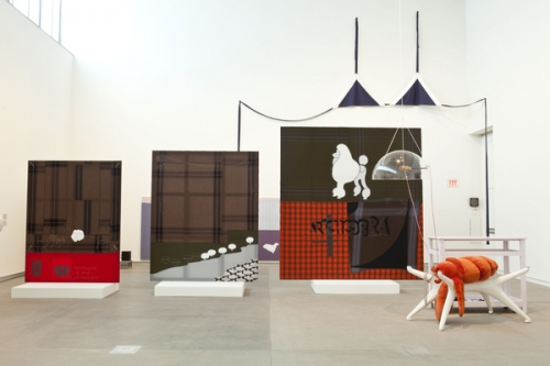 Installation view from von Bonin's 2011 show at the Kemper Art Museum. Features three fabric paintings increasing in size from left to right. all are primarily brown, red, and a deep green. they are mounted on small white platforms in the center of the gallery. to the right is a stuffed lobster over a three-pronged table stand. a large, navy fabric bikini top hangs on the wall in the background