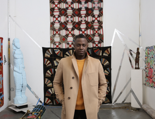 Sanford Biggers, the artist, in front of his antique quilts and African style sculptures