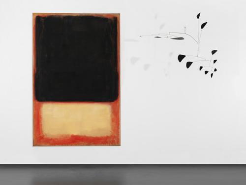 Installation view of a black and yellow Rothko painting next to a black mobile sculpture by Calder that is suspended from the ceiling.