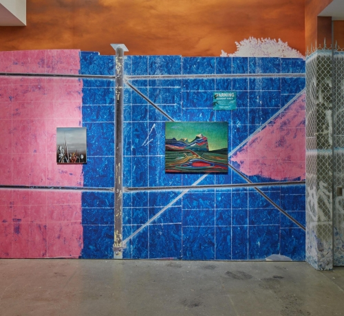 this is an image of the exhibition SUPERUNKNOWN HELD AT Nahmad Contemporary. It features as a wall paper a gigantic photo by Urs Fischer which represents loosely a construction site,  scaffolding and a fence, the colors are rich, pink on the left and dark blue on the right.  Two small paintings are featured in the center on bey Yves Tanguy and the other by Max Ernst.