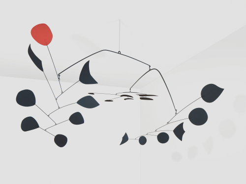 This is an image of a Calder mobile that is currently exhibited at Neue National Galerie for the exhibition Calder Minimal/Maximal. It shows a mobile with black elements only one elements is red. the title is Triumphant red.