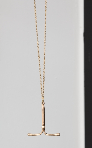 A gold-plated IUD necklace on a gold chain
