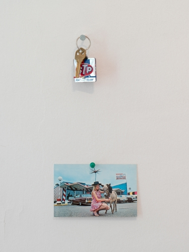 An installation that shows a postcard hung below a set of keys