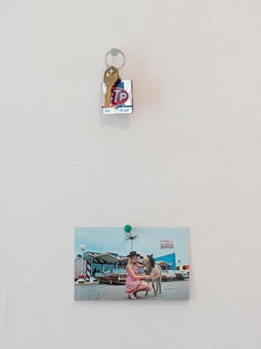 An installation that shows a postcard hung below a set of keys