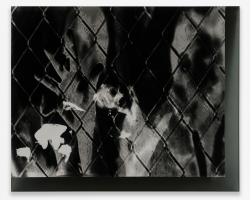 A black and white photograph of a chainlink fence with hands behind it, adjusted digitally to be shadowy