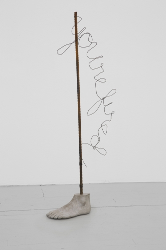"A sculpture of a concrete foot and a rebar pole sprouting from it. In wire, the words ""You're fired"" are written hanging off the side"