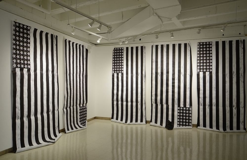 An installation of 5 black and white printed american flags
