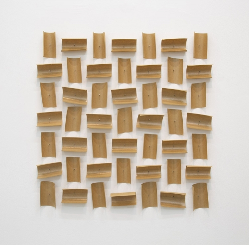 An arrangement of brown paper tape pieces pinned to the wall, 49 total