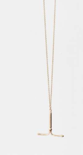 An image of an IUD made of brass, strung on a gold chain