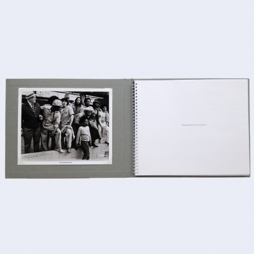 An open book with a black-and-white image at left, and the book's title at right.