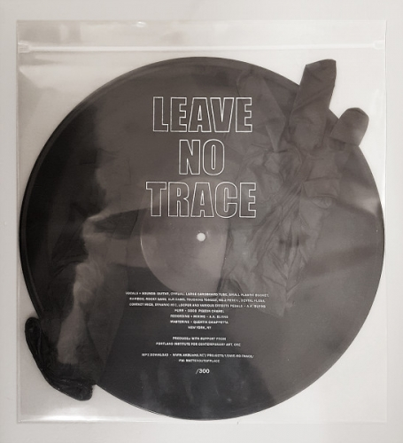 A record in plastic bag with LEAVE NO TRACE written on the front, black record
