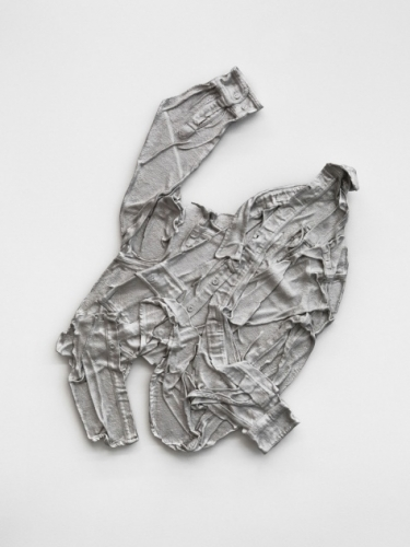A shirt made of aluminum, hung on the wall, wrinkled