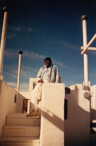 """This image depicts the artist, Noah Purifoy, sitting in his artwork, """"The White House"""", which was made from 1990 to 1993."""