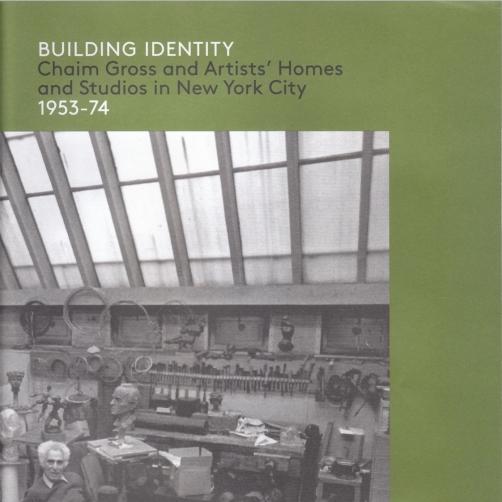 """Exhibition catalogue cover, bearing a black and white photo of Chaim Gross sitting in his studio surrounded by his art and his tools, placed on top of a green background. The top of the cover is the title of the catalogue, """"BUILDING IDENTITY"""" in white, followed by """"Chaim Gross and Artists' Homes and Studios in New York City"""" in grey, and """"1953-74"""" in white."""