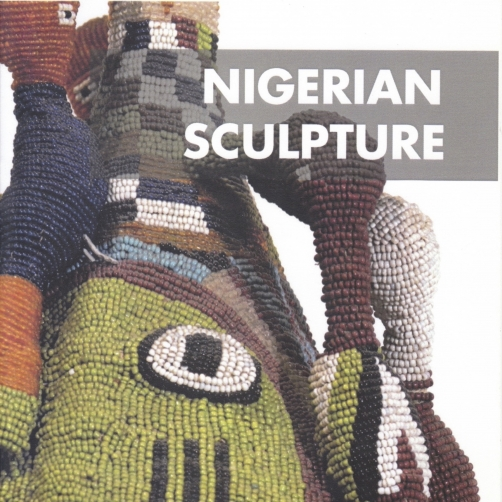 """Exhibition catalogue cover, bearing a a cropped, zoomed in photograph of a Yoruba crown, comprised of colorful beads and fabric, the front of which bears the depiction of a green, beaded face. Superimposed on the top right of the cover is a band of grey, placed on top of which is the title of the catalogue in white, """"NIGERIAN SCULPTURE""""."""