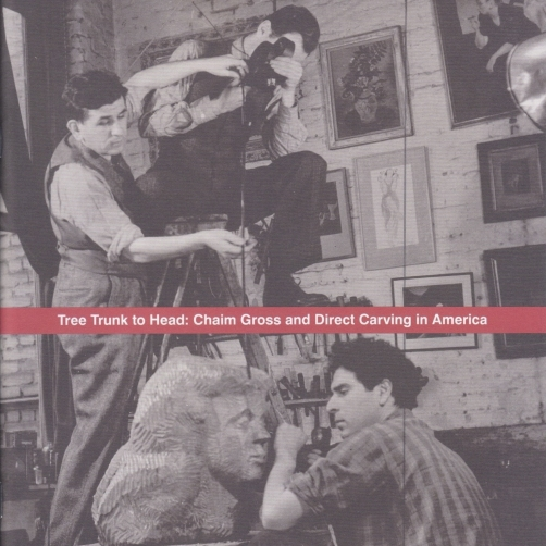 """Exhibition catalogue cover, bearing a black and white photograph of director Lewis Jacobs and cameraman Leeo Lances, filming Chaim Gross carve a bust of a woman in his studio. At the center of the image is a horizontal red band, bearing the title of the catalogue, """"Tree Trunk to Head: Chaim Gross and Direct Carving in America""""."""