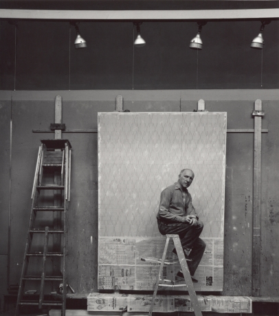 image of a man sitting on a ladder with a painting in progress in the background