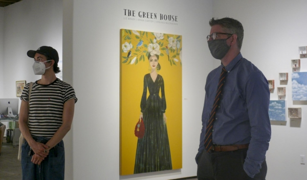 """Jeremy Tesmer, right, and Sam Johnson looking at art on the walls of the Sullivan Goss American Gallery on Oct. 4 in Santa Barbara, Calif. The gallery has remained open with restrictions during the pandemic and exhibits show artists from all across the country. The painting in the background """"The Green House"""" was made by local artist Erika Carter. (Madeleine Sydkvist)"""
