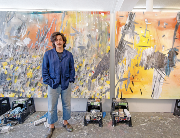 The artist Dashiell Manley in his studio next to his abstract canvases