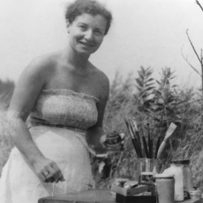 Black and white photo of a woman standing in a field of tall grass wearing a sleeveless, white summer dress. Beside her to the right is a small table with paint brushes and other art supplies.