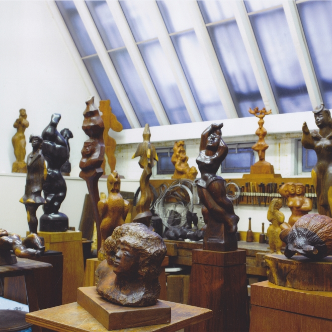 A photo of a high ceilinged, bright, white studio with a large slanted skylight window with a cluster of sculptures in various shades of wood. Almost all of the sculptures depict humanoid faces and abstracted, smooth renditions of the female form.