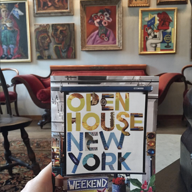 Picture of a pamphlet with the partially visible hand of someone holding it visible. The pamphlet has bright colors, collage styling, and geometric lettering. In the background vibrant pieces of art are framed on the wall and you can seen antique red velvet love seat.