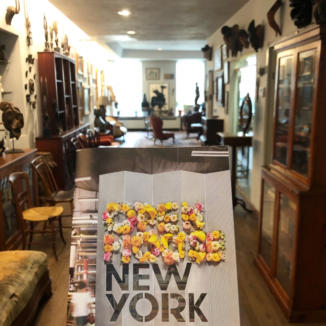 """Brochure with bold, black geometric lettering that says """"New York"""" on the front. In the background is the hallway of a room with dark wood floors and cabinets lining the sides. Sculptures of masks are hanging on the wall to the right and there a chairs scattered about the space."""