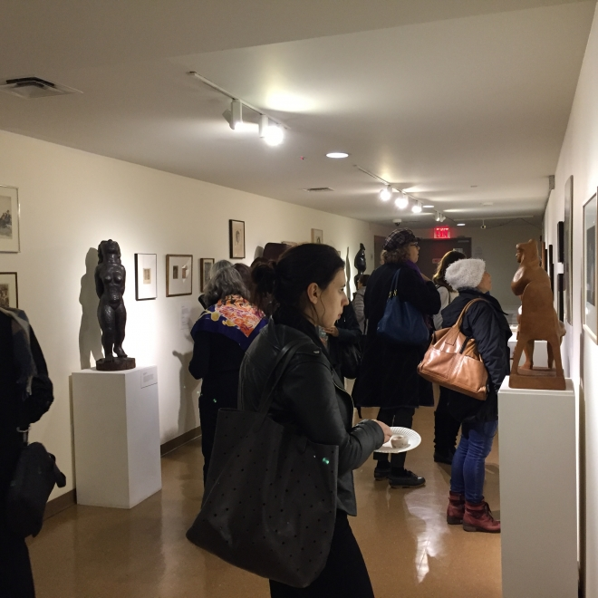 Photo of a gallery with white walls and a light brown floor. The gallery has a low ceiling and adults in dark winter clothes are milling around. On the walls are various pieces of art work in dark brown frames and several large sculptures in shades of brown are visible. To the left of us is a dark colored humanoid sculpture.