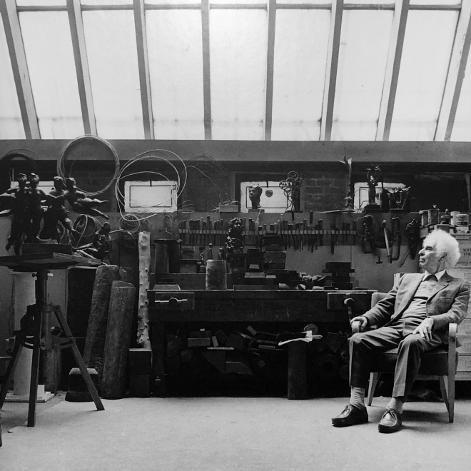 A black and white photo of an elderly Chaim Gross with prominent fluffy white hair wearing a suit sits to the left of us. He is facing sideways away from us, looking at his large collection of tools, work bench, and a sculpture of a cluster of female forms in playful motion.