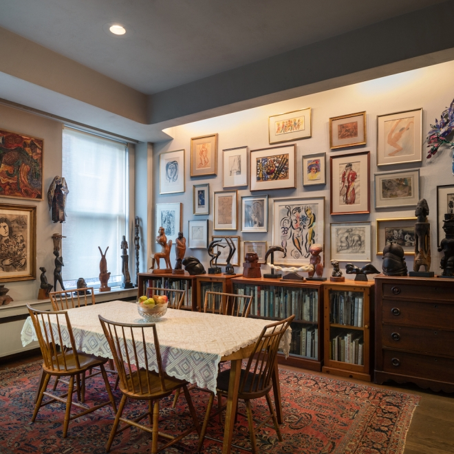 A light brown wood dining table with matching color chairs and a white cloth on top of it is in the front left closest to us. On the top of the table is a glass bowl with several types of fruit inside, and there are short, hip high bookshelves and a crowding of framed artworks lining the wall behind it. On top of the bookshelves are small sculptures in different shades of wood.