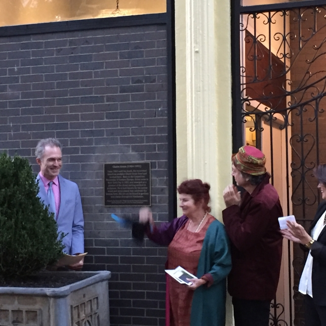 Mimi Gross stands in the center of three other adults in front of a brick building with yellow lining around the doorway. Her right hand is blurred and in motion and she holds two black and white pieces of paper in her left hand.