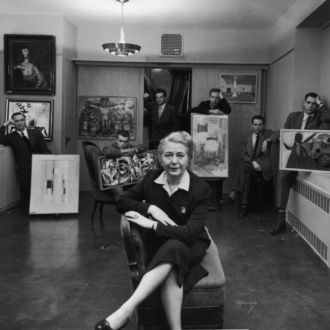 Black and white photo of an older woman seated in the front center, wearing a black suit dress and crossing her legs confidently over her chair. Behind her are six young men, four seated and two standing, wearing dark suits and either holding large pieces of art work or placed near or next to them.