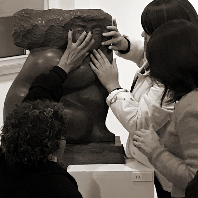 Close up black and white photo of three adults with dark hair touching the face of a large, wide, wood sculpture of a humanoid subject with a blocky, smooth body shape.