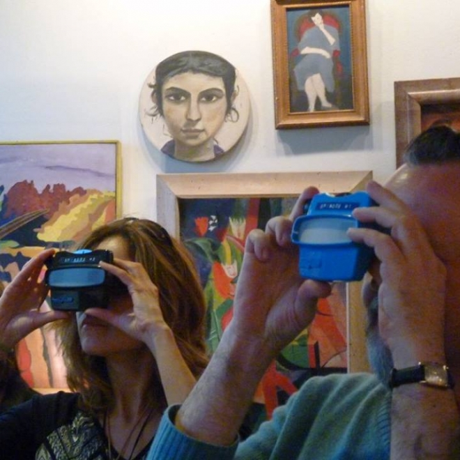 Two adults stand very close to us with only their heads and hands holding small cameras showing. Behind them brightly colored artwork covers a white wall.