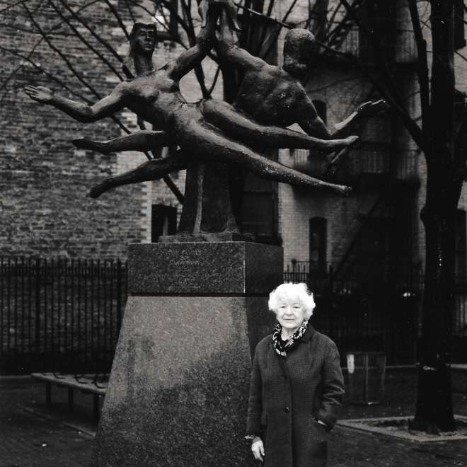 A black and white photo of an elderly Renee Gross in a dark winter coat with bright white hair standing in front of a large outdoor sculpture. The sculpture features two identical female forms laying sideways with their left hands raised and touching. In the background of the photo you can see apartment buildings made of brick.