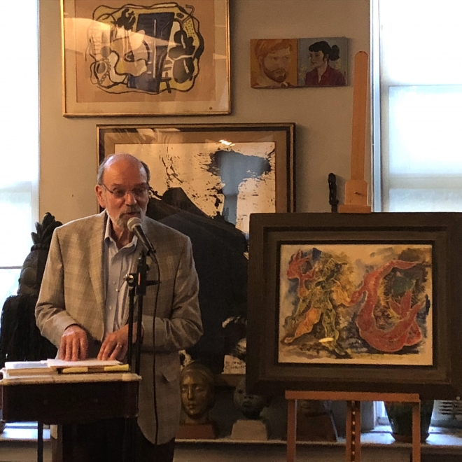 An older man with glasses and a short beard in a grey plaid suit stands to the left of us at a podium speaking into a microphone. To the right of him is a vibrant painting of organic, humanoid forms in a dark brown frame on an easel.