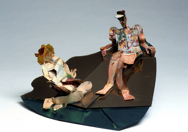 A sculpture of an adult man and a woman made of thin, brightly painted material sits on a dark organic shaped base. The woman has blonde hair and is turned upwards to face the male sculpture who is sitting up higher in the composition. The man looks downwards, his face in shadow.