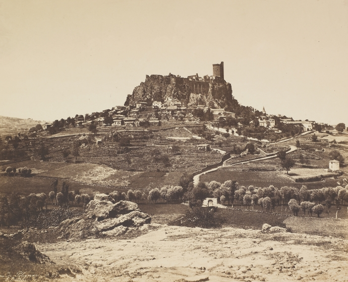 "Édouard BALDUS (French, 1813-1889) ""Château de Polignac"", 1850s Coated salt print from a paper negative 32.6 x 44.7 cm mounted on 44.9 x 59.9 cm paper Signed ""E. Baldus."", titled ""Château de Polignac"" and numbered ""No 67"" in the negative. ""E. Baldus"" blue signature stamp on mount."