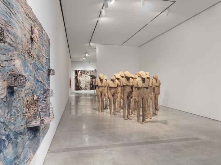 Installation view of large scale textured canvas with birdcages by Anselm Kiefer and group of multiple burlap and resin life-size standing figures with different heads by Magdalena Abakanowicz along with her textiles and a steel bird sculpture