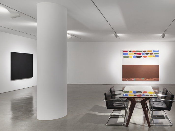Installation view of black oil painting on canvas by Ad Reinhardt and an oil painting by Adolph Gottlieb of multiple color swatches and brown