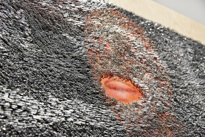 """Detail of Wilmer Wilson IV's """"S AM S"""" (2017), composed of thousands of industrial staples that cover all but small sections of large photographs."""
