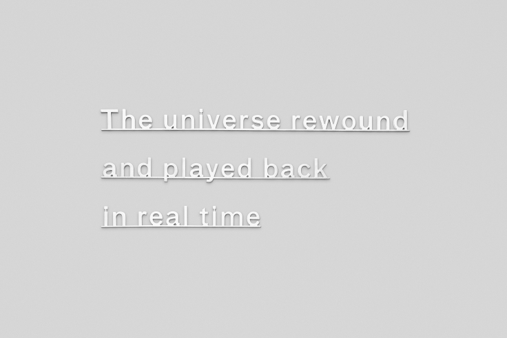 """Silver letters on a wall that read: """"the universe rewound and played back in real time"""""""