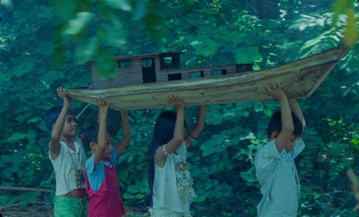 Group of children carrying a wooden boat in a jungle