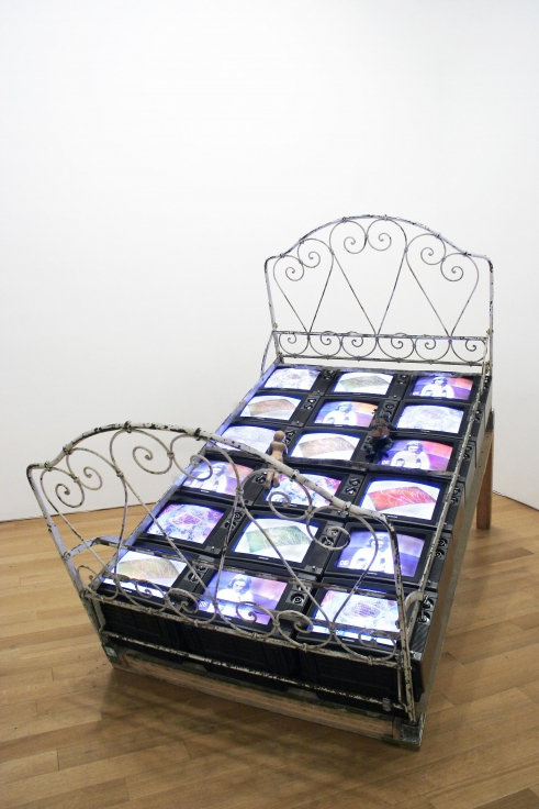 , NAM JUN PAIK,TV Bed, 1971/72, Three channel color video, eighteen TVs, antique metal bed frame, wood, puppets, 90 1/2 x 78 3/4 x 59 in. (230 x 200 x 150 cm)